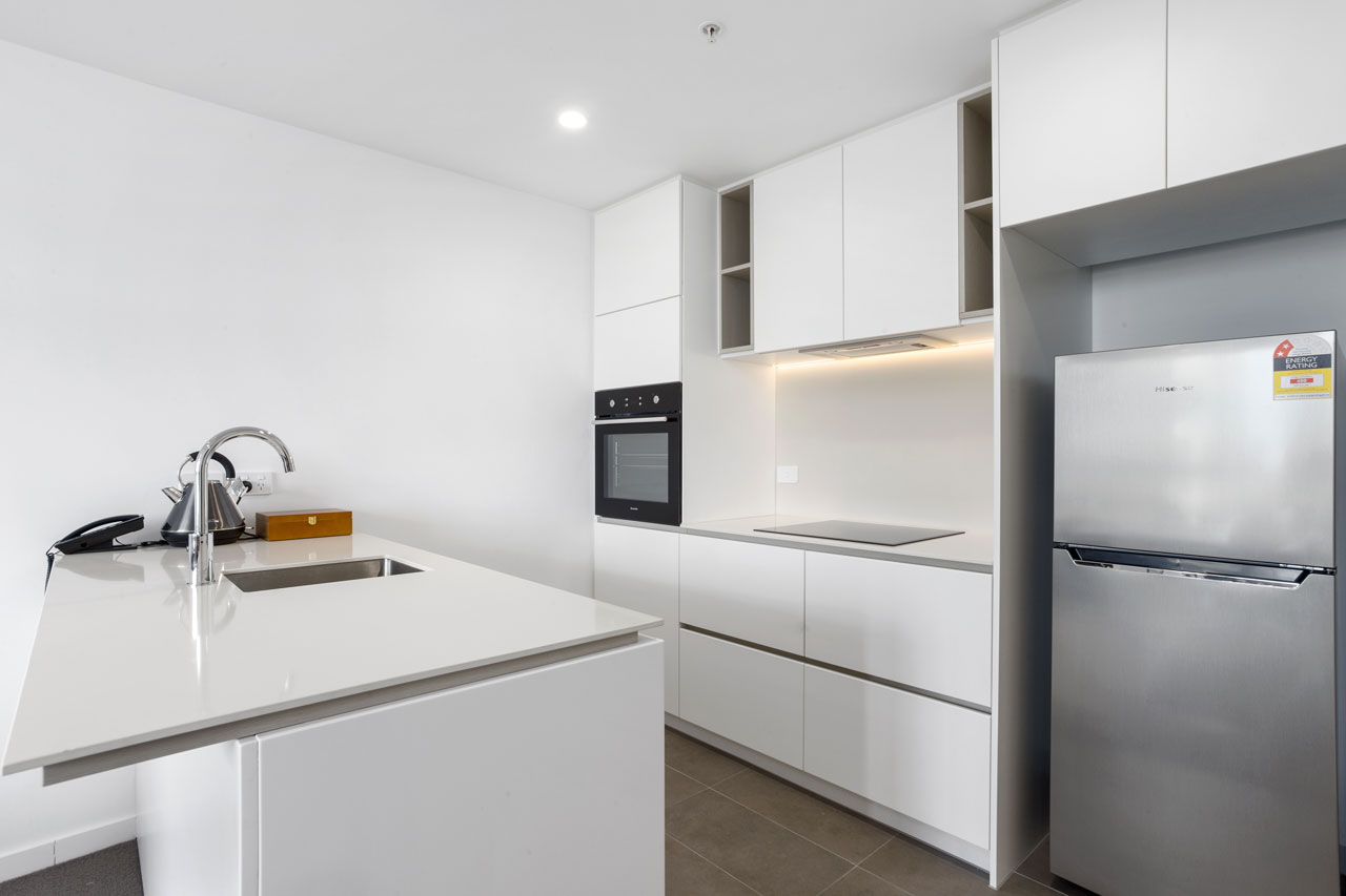 Kitchen and fridge at 1 bedroom king - The Sebel Moonee Ponds