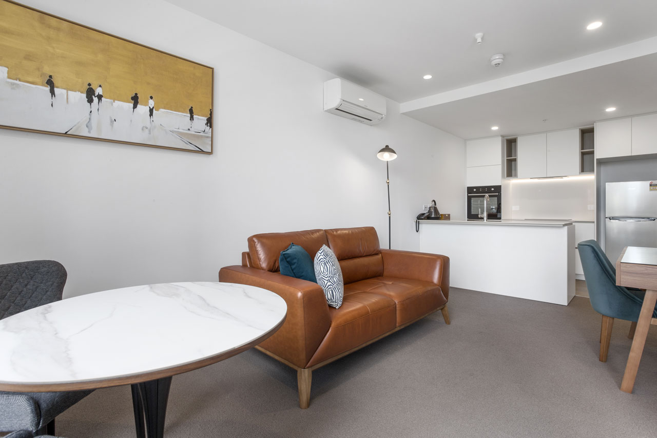 Lounge and kitchen in 1 bedroom apartment king at The Sebel Moonee Ponds