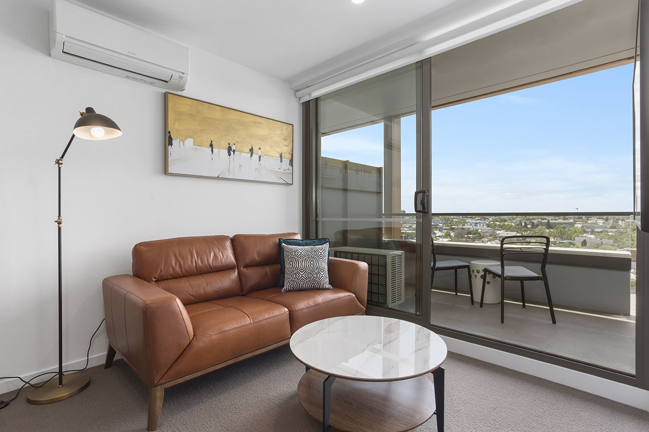 Sofa and artwork plus view of balcony and beyond at The Sebel Moonee Ponds