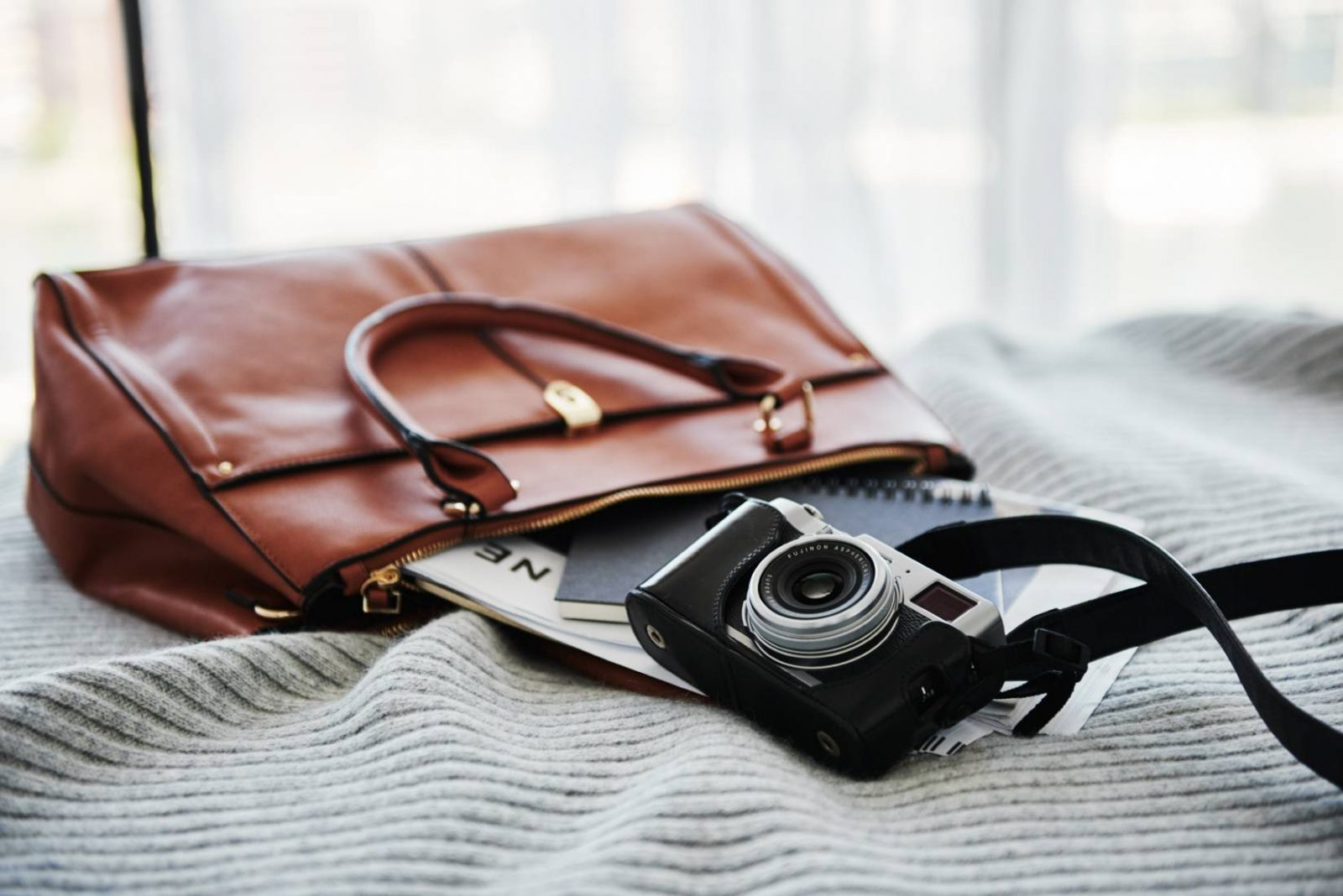 Tan leather handbag with camera laying on bed