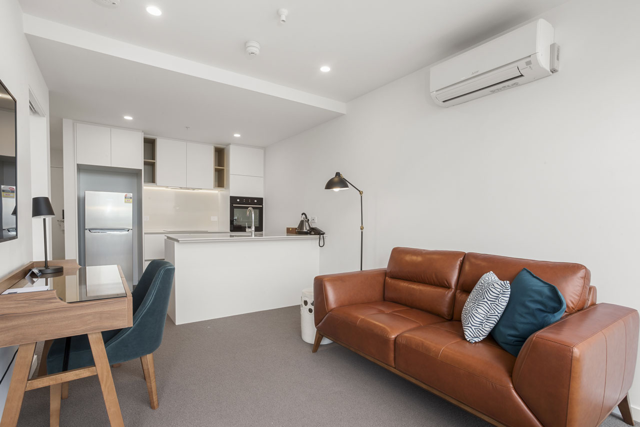 Lounge and kitchen in 1 bedroom with king apartment at The Sebel Moonee Ponds